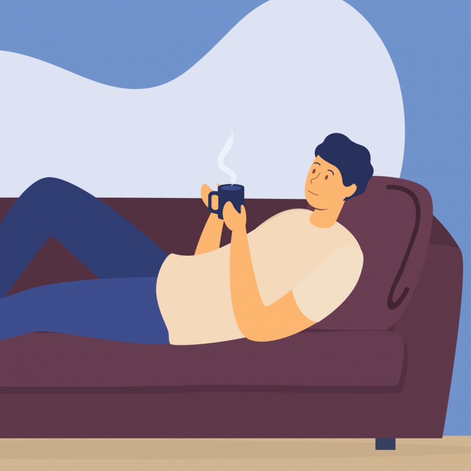 A person resting on a sofa with a cup of hot drink in hands
